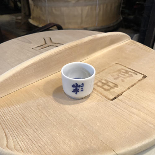 a sake cup sitting on a barrel